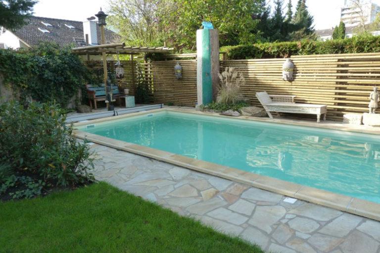 Helle Beckenrandsteine umrahmen einen Swimmingpool von Pro Pool