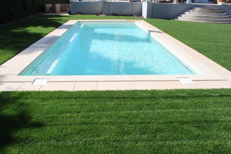 Pool umrahmt von hellen Beckenrandsteinen und grüner Wiese