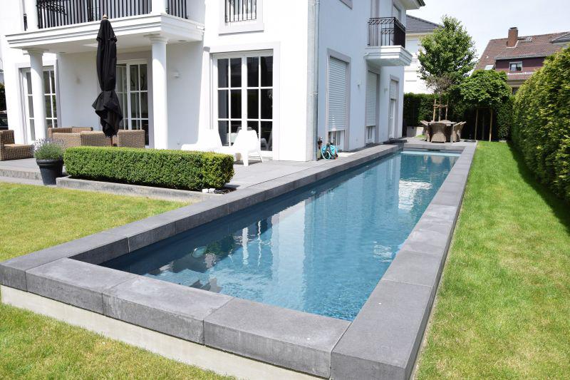 Langer Swimmingpool mit grauen Beckenrandsteinen