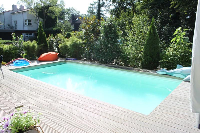 Pool umrahmt von hellem Holz und Bäumen