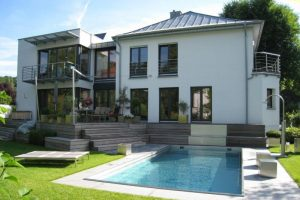 Terrassenabgang führt zu großem Swimmingpool im Garten