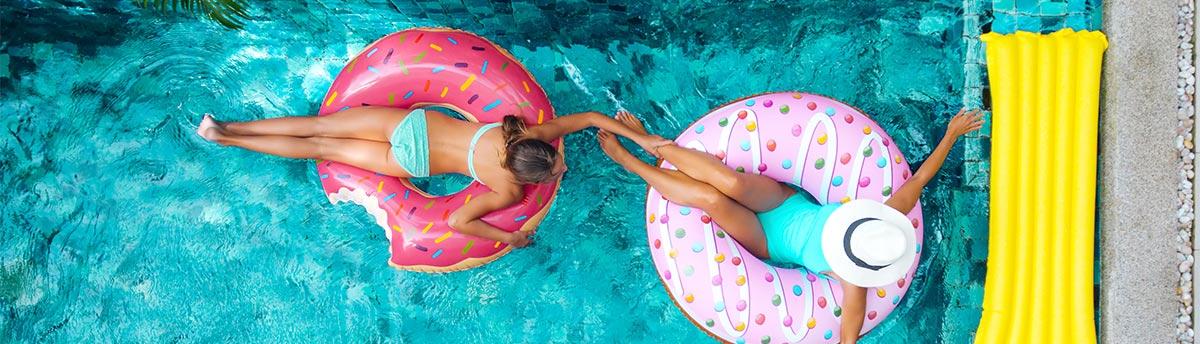 Frauen entspannen im Pool auf aufblasbaren Dontus