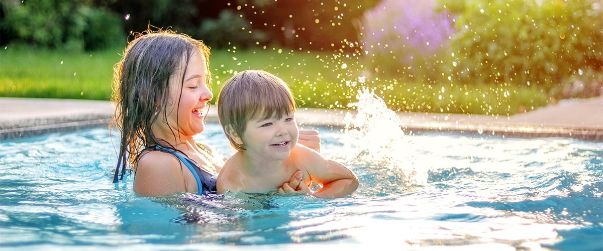 Kinder spielen und planschen im Pool