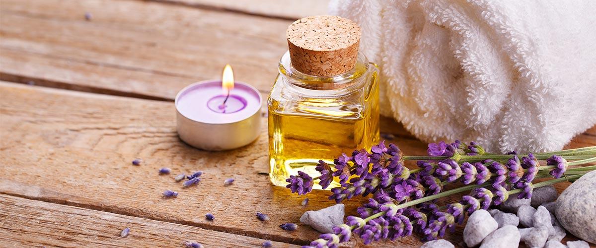 Lavendel neben einem Handtuch, Aromaöl und Duftkerze in einer Sauna.