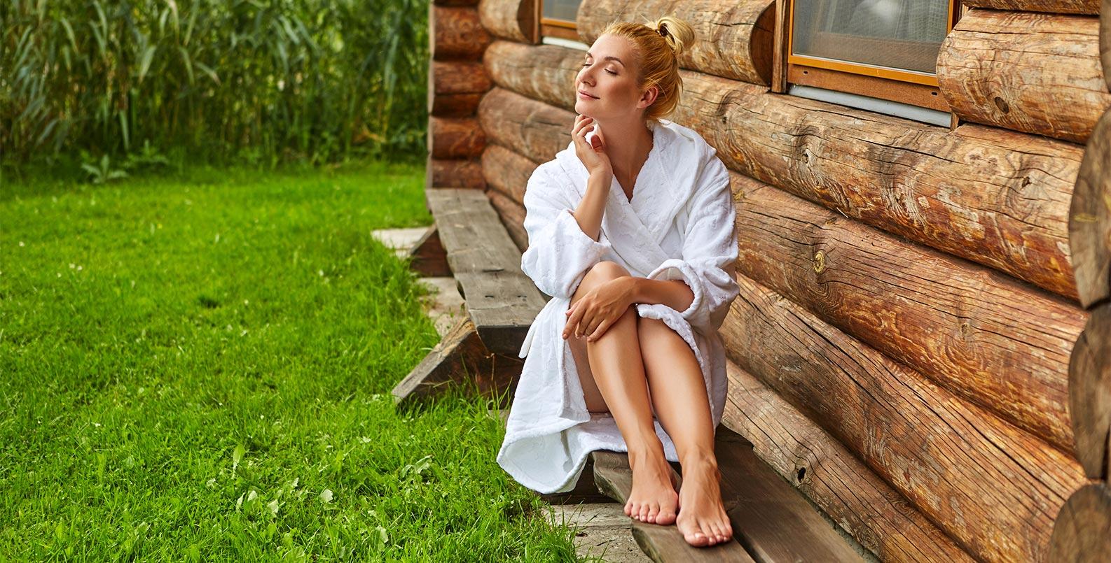Frau entspannt draußen im Garten nach Saunieren.