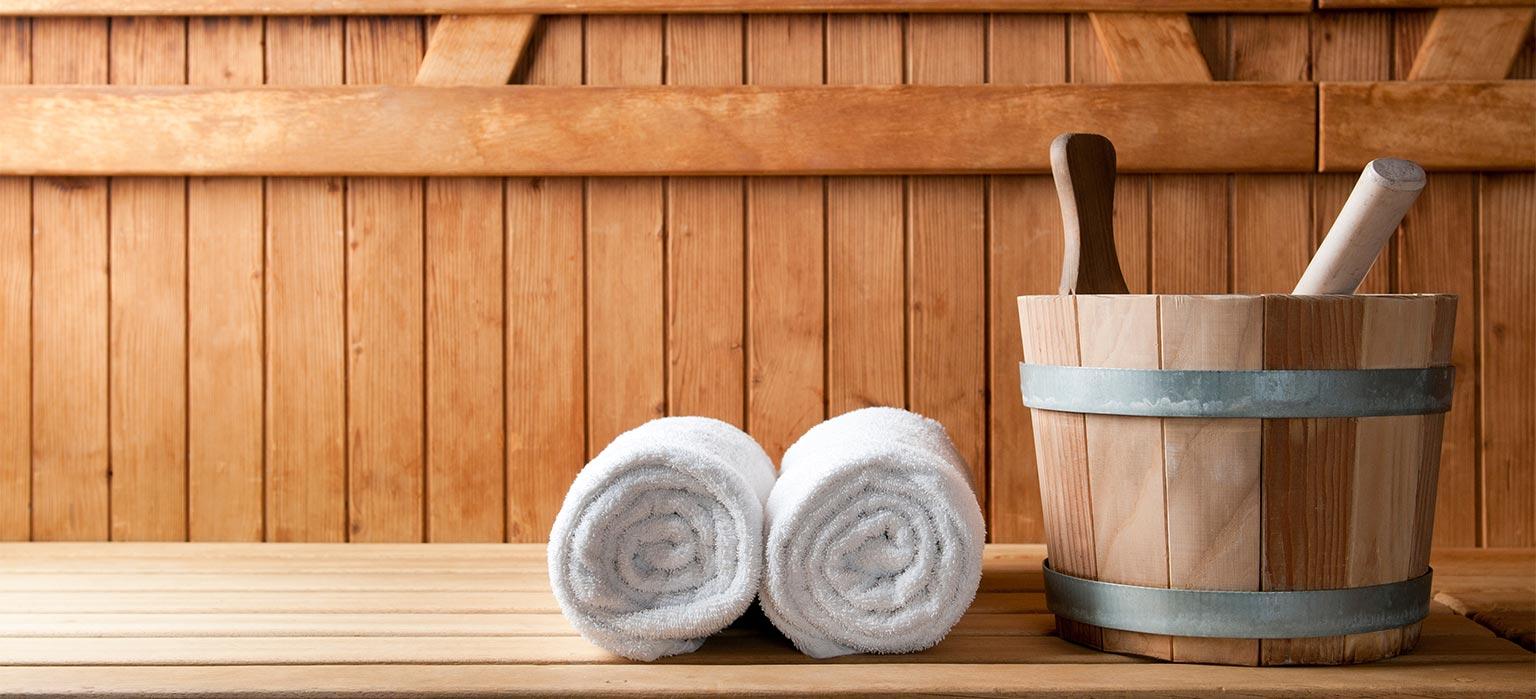 Gerollte Handtücher liegen neben Eimer auf Saunabank.