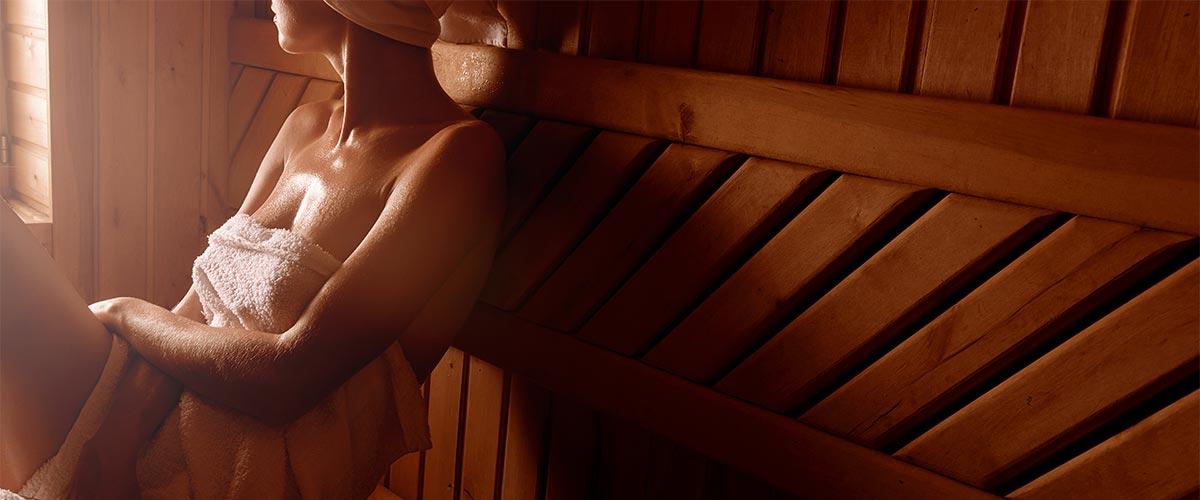 Frau sitzt in Sauna und schwitzt.