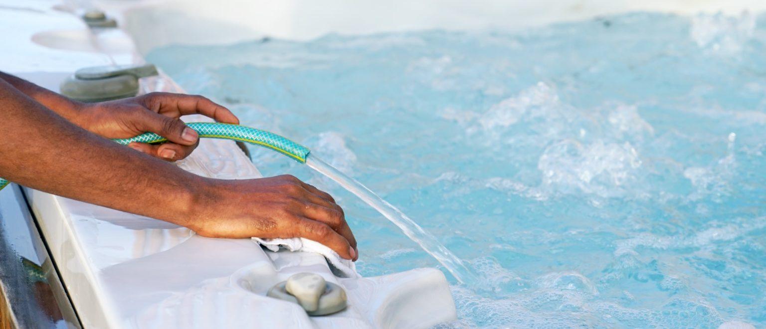 Mann tauscht Wasser im Whirlpool aus.